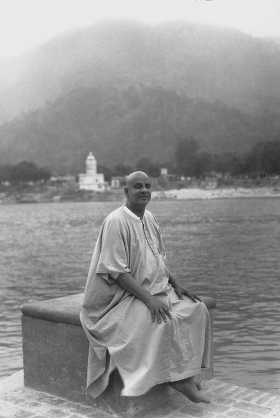 Swami Sivananda sitting by the Ganges in deep contemplation about life