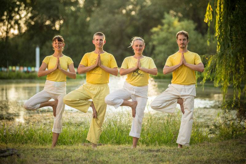4 students practice Tree Pose by the pond