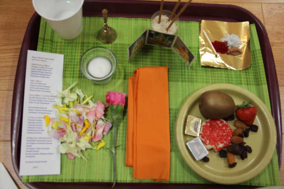 Puja tray with all items - incense, lamp, bell, flowers, water, powders, cloth, prasad