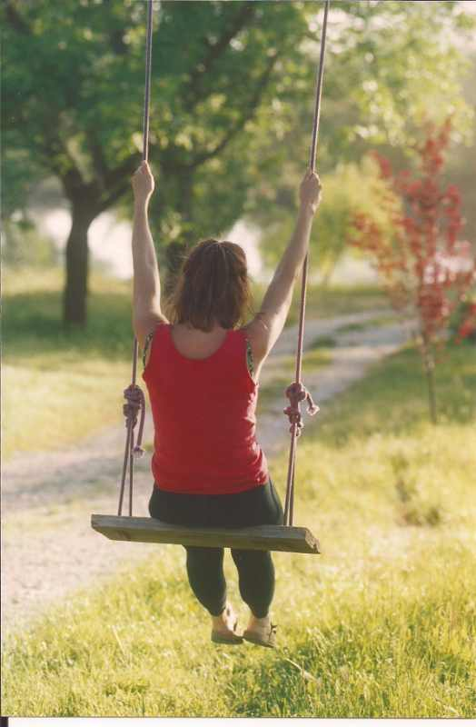 A woman on a swing from behind enjoying the ride.